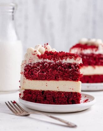 A slice of red velvet cheesecake on a white plate from the side with a fork in front.