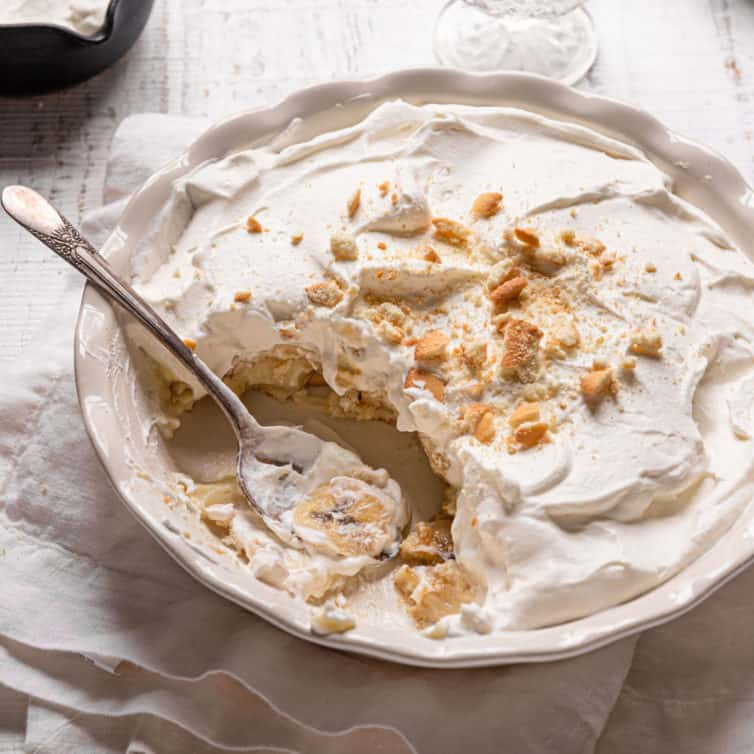 Banana pudding in a pie dish topped with vanilla wafers with a spoon in the front.