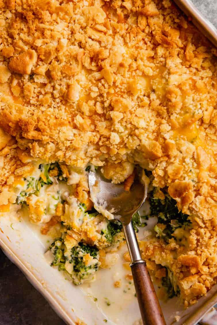 A casserole dish with broccoli casserole with a spoon with a wooden handle and a scoop of broccoli casserole taken out.