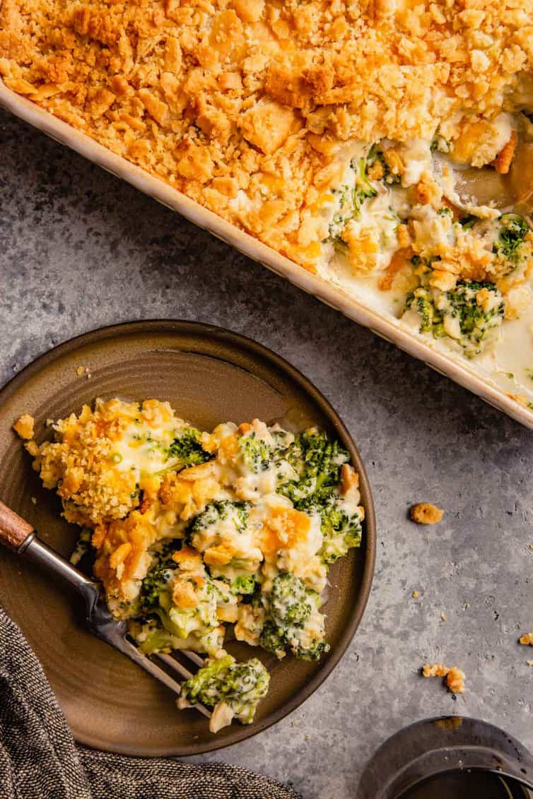 A top down picture of broccoli casserole on a brown plate with a fork to the left and a casserole dish to the right.