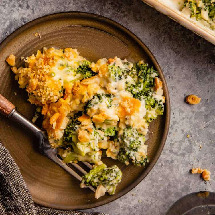 A brown plate with a scoop of broccoli casserole with a fork with a wooden handle on a grey counter.