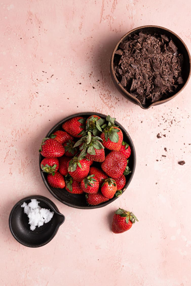 A bowl of chocolate in the top right, a bowl of strawberries in the middle with a strawberry to the side, and a small bowl of coconut oil in the bottom left on a pink counter.