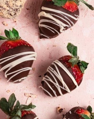 Chocolate strawberries drizzled with white chocolate on a pink counter.