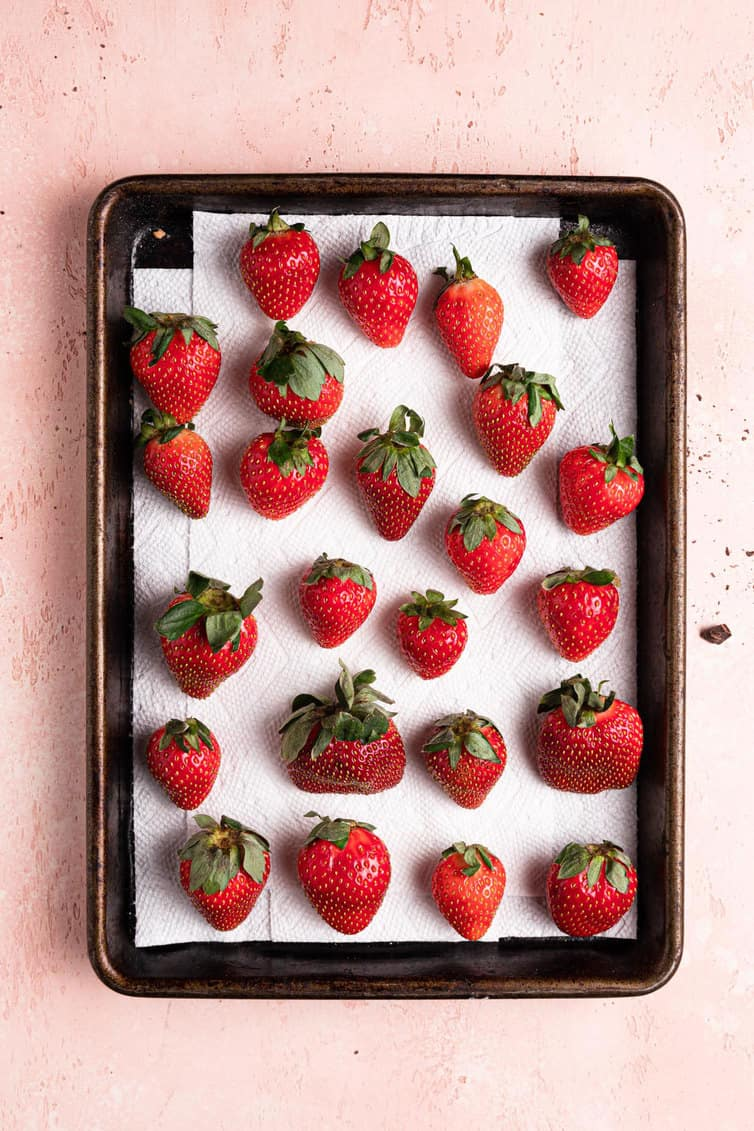 A paper towel lined baking sheet with fresh strawberries on a pink counter.