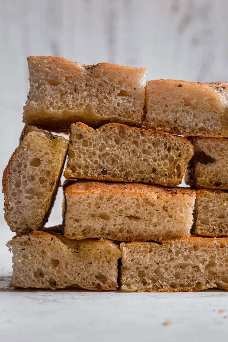 A stack of sliced focaccia layered like bricks on a white counter.