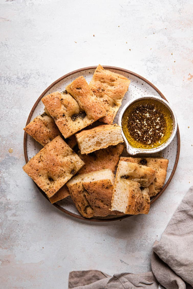 A top down photo of a small plate with a brown rim filled with a pile of sliced focaccia and a small herb oil bowl to the right.