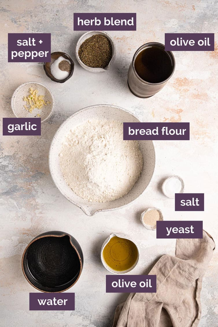 Labeled ingredients for focaccia on a white counter.