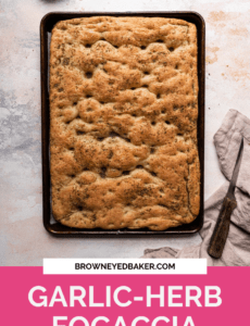A sheet pan with fresh baked focaccia on a white counter with a pink rectangle at the bottom and the words Garlic- Herb Focaccia at the bottom.