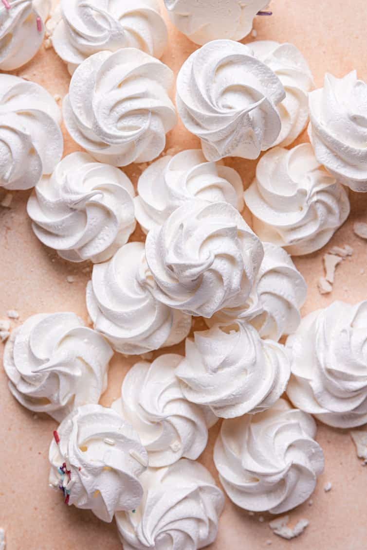 A pile of piped meringue cookies baked and on a pink counter.