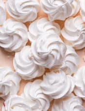 A top down photo of a pile of white meringue cookies with one on the top in the center.
