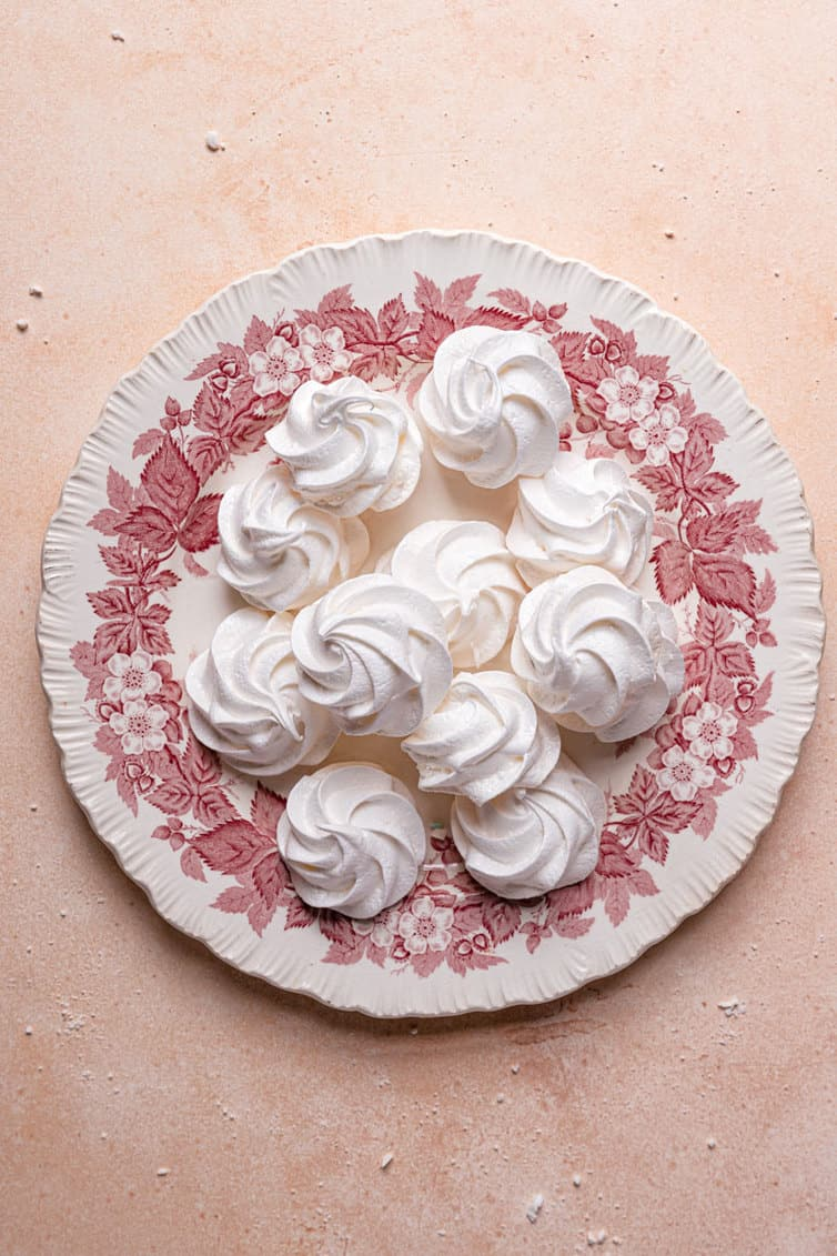 A pink and white plate with a pile of meringue cookies on a pink counter.
