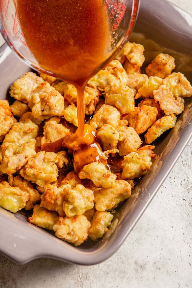 A baking dish filled with fried chicken pieces with sweet and sour sauce being poured over.