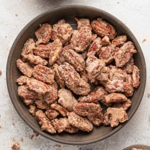 A square photo with candied pecans in a brown bowl on a white counter.