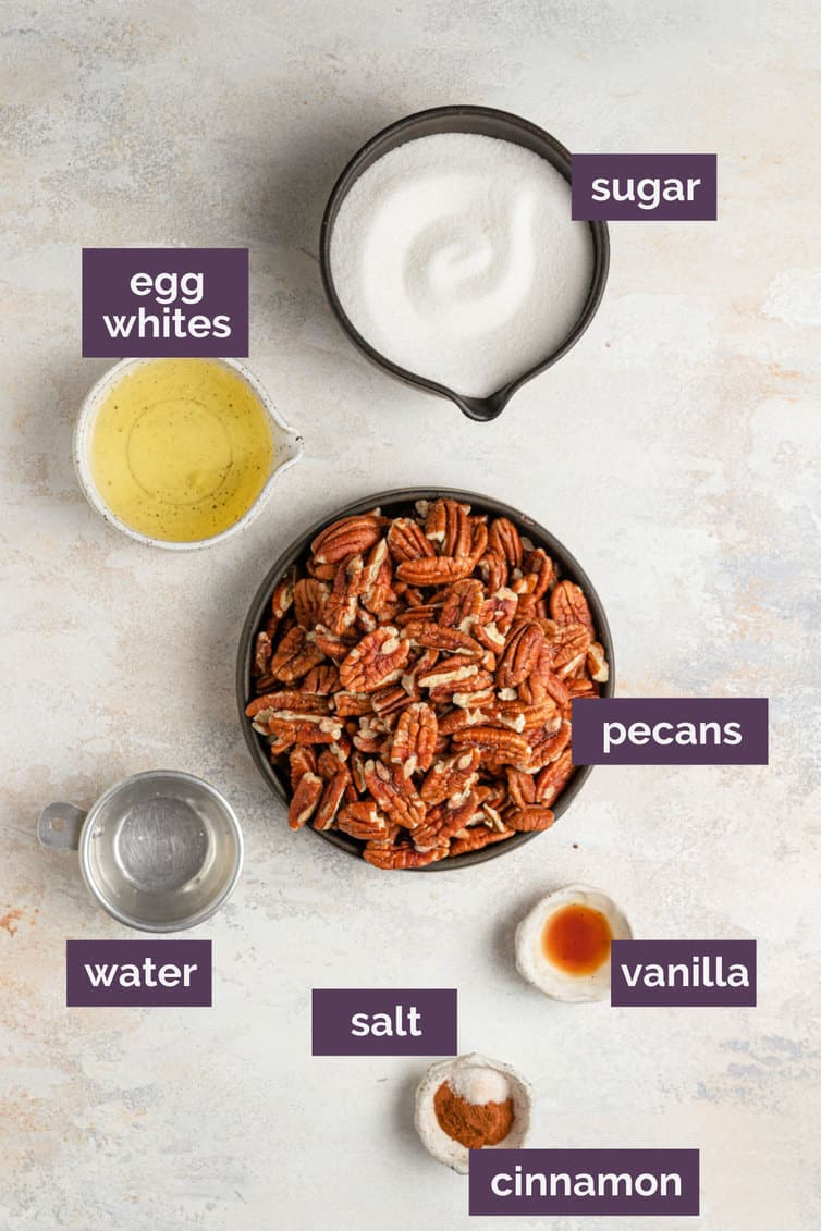 The ingredients for candied pecans on a white counter labeled with purple labels.