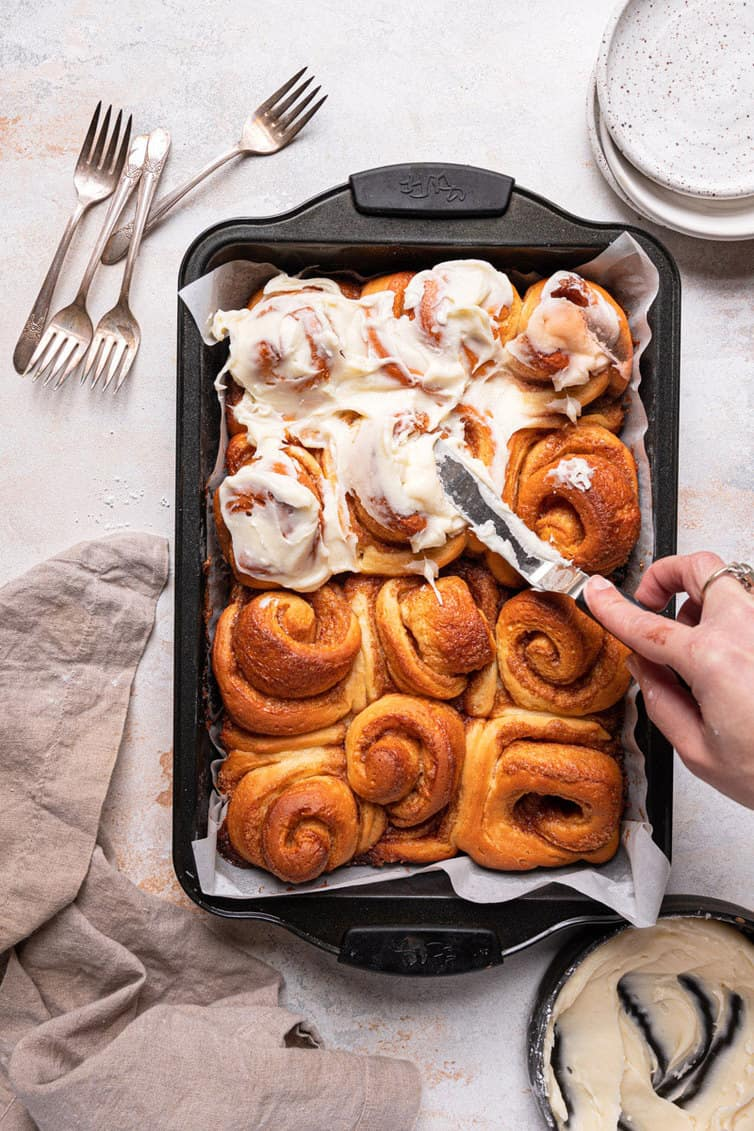 A hand with an offset spatula spreading cream cheese icing on a pan of cinnamon rolls.