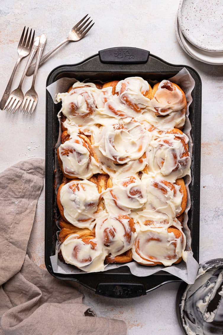 A rectangular baking pan lined with parchment paper with cinnamon roll covered in cream cheese icing on a counter with a stack of plates in the back right.