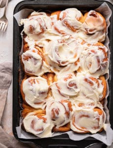 A baking pan with cinnamon rolls covered in cream cheese frosting with a stack of forks in the top left.