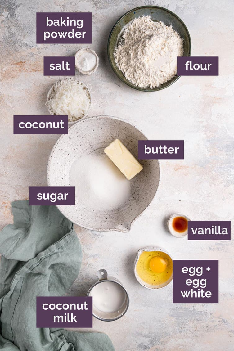 Ingredients for coconut cupcakes in bowls labeled with purple labels.