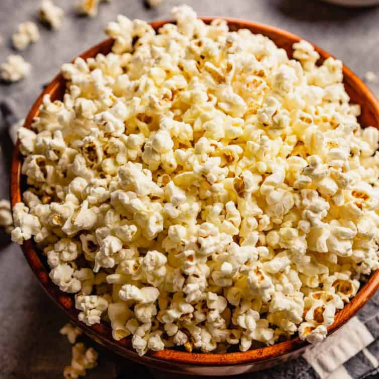 A brown bowl with fresh, homemade popcorn and some pieces of popcorn scattered on the counter.
