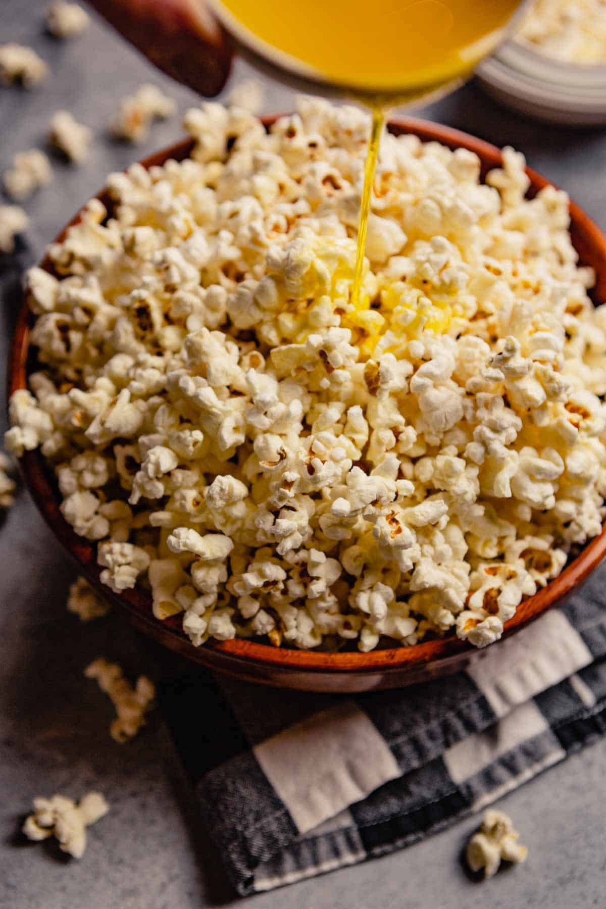 Bowl of popcorn with clarified butter being drizzled over top.