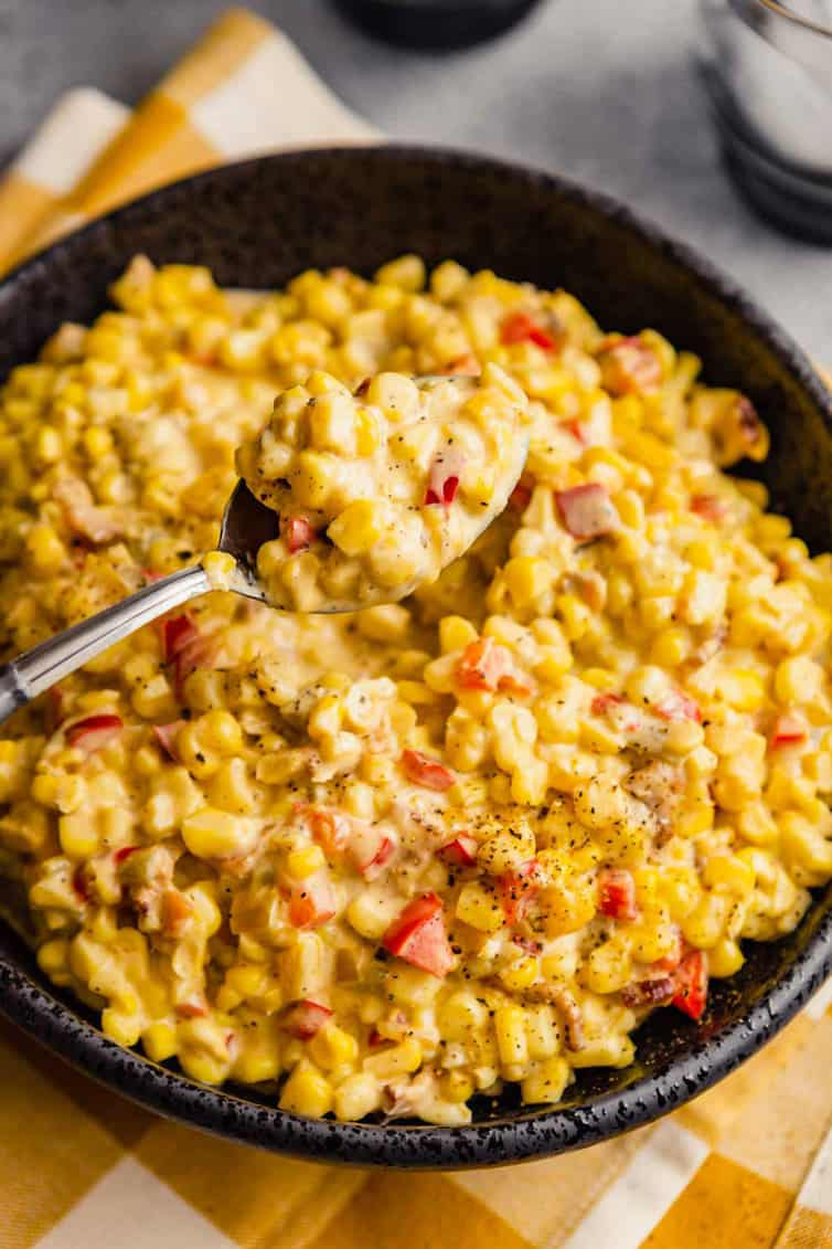 A silver spoon with a scoop of Mexican corn salad over a large bowl of corn salad on a yellow and white towel.