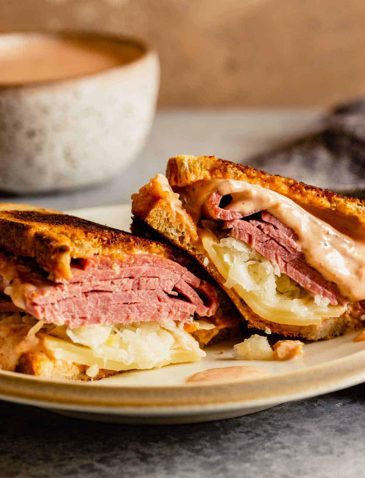 A Reuben sandwich cut in half on a plate.