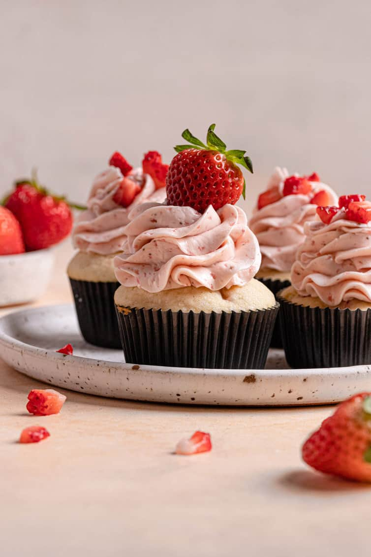 A white plate with a rim holding four strawberry cupcakes topped with fresh strawberries on a pink counter.