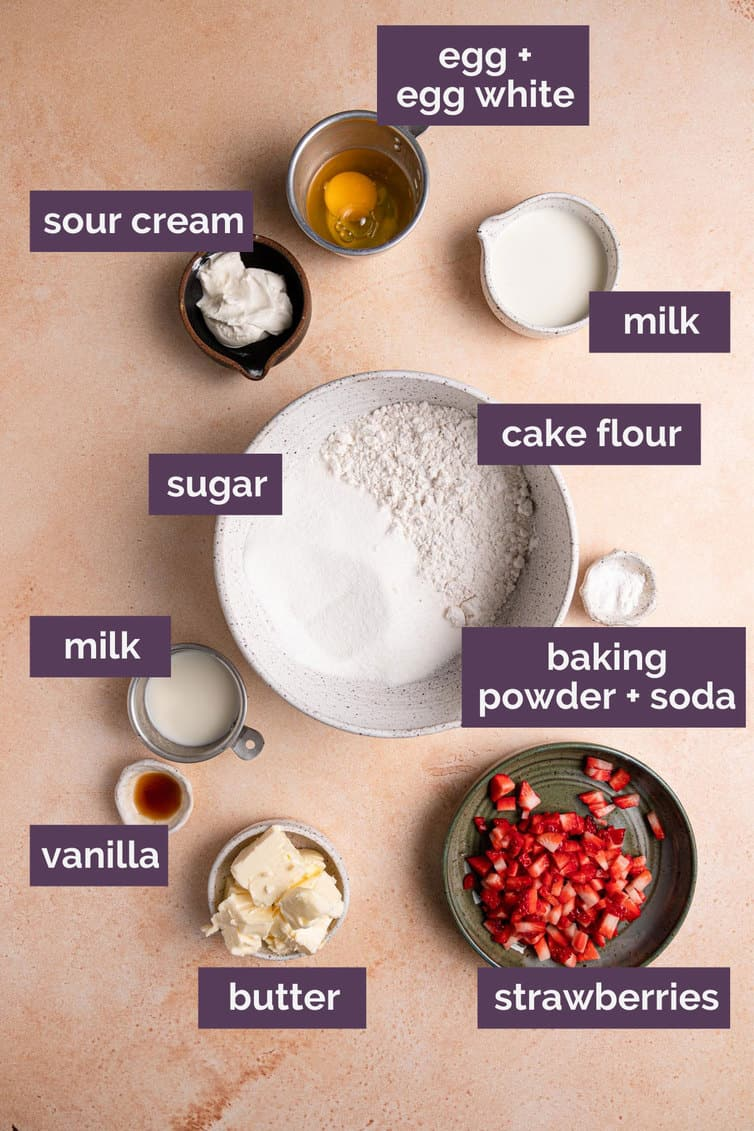 Ingredients for strawberry cupcakes on a pink counter with purple labels.