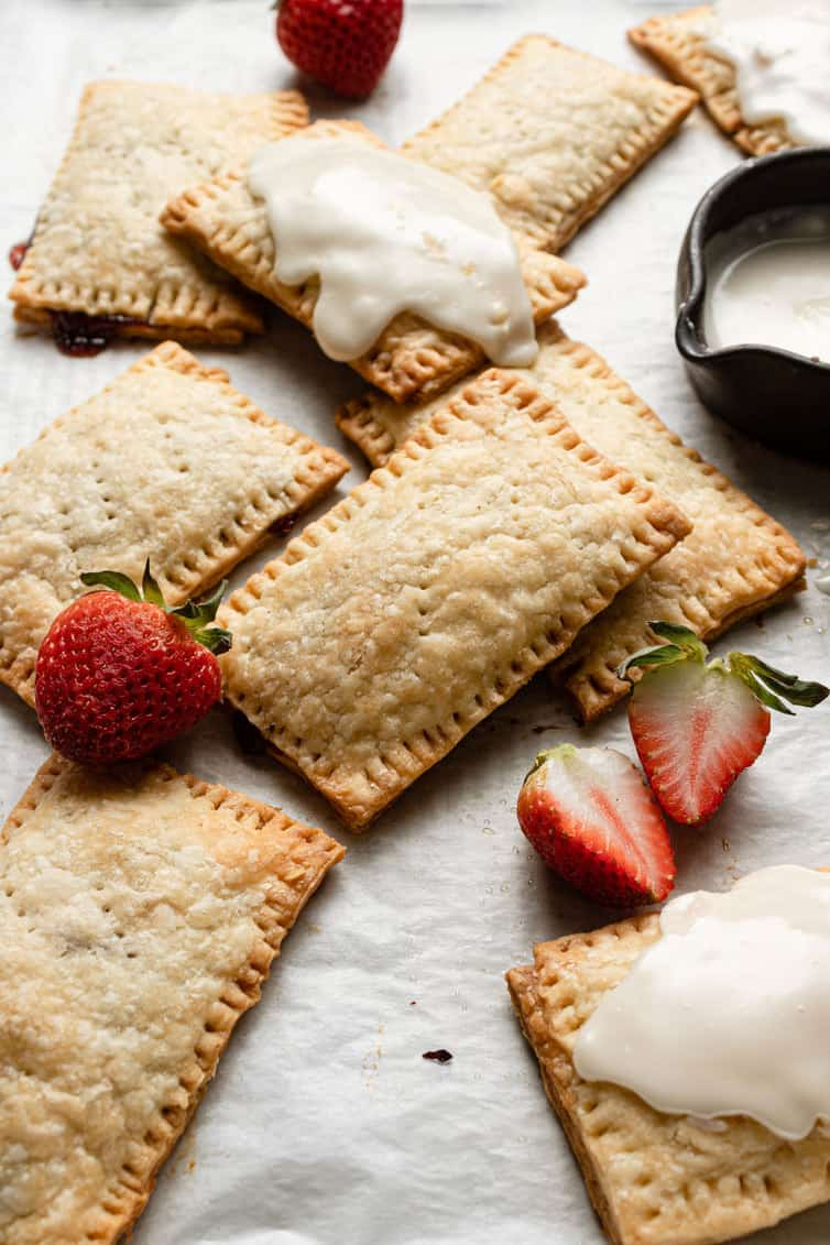 Strawberry pop tarts on a parchment paper with some fresh strawberries and a small spouted bowl with homemade icing.