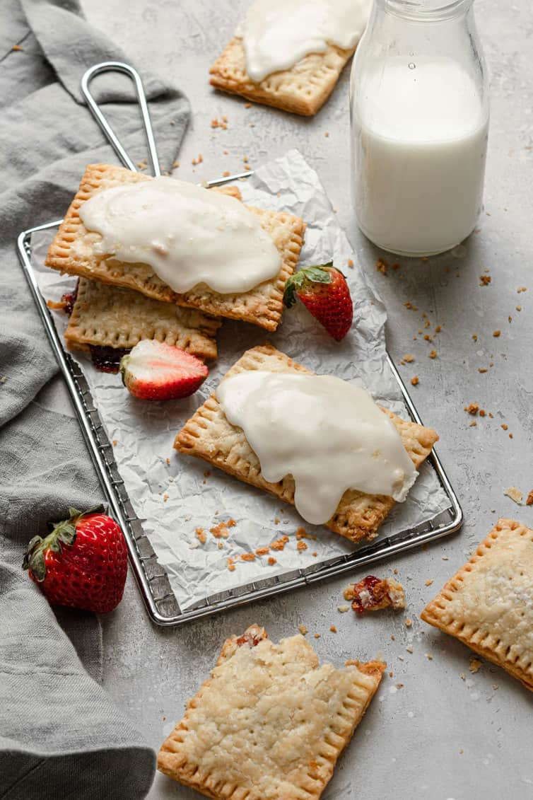 Iced homemade strawberry pop tarts on a baking sheet with parchment paper with a glass of milk to the right and fresh strawberries around.