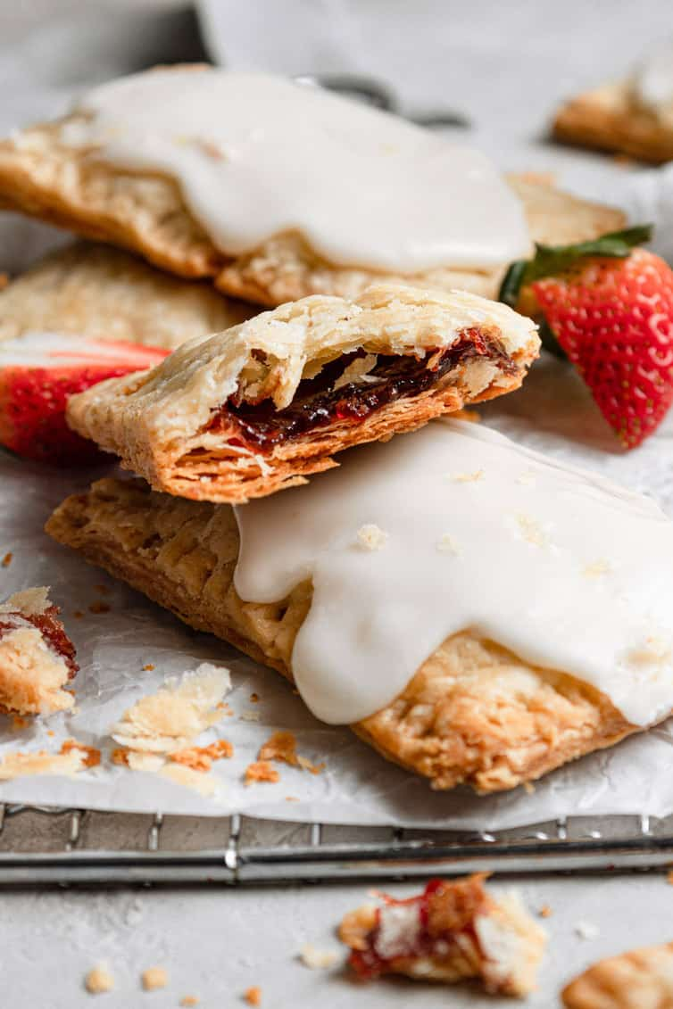 A close up of the inside of a strawberry pop tart on top of iced pop tarts next to fresh strawberries.
