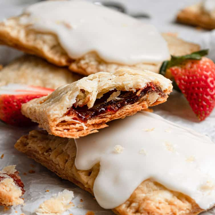 Half of a strawberry pop tart on top of iced homemade pop tarts on a piece of parchment paper.