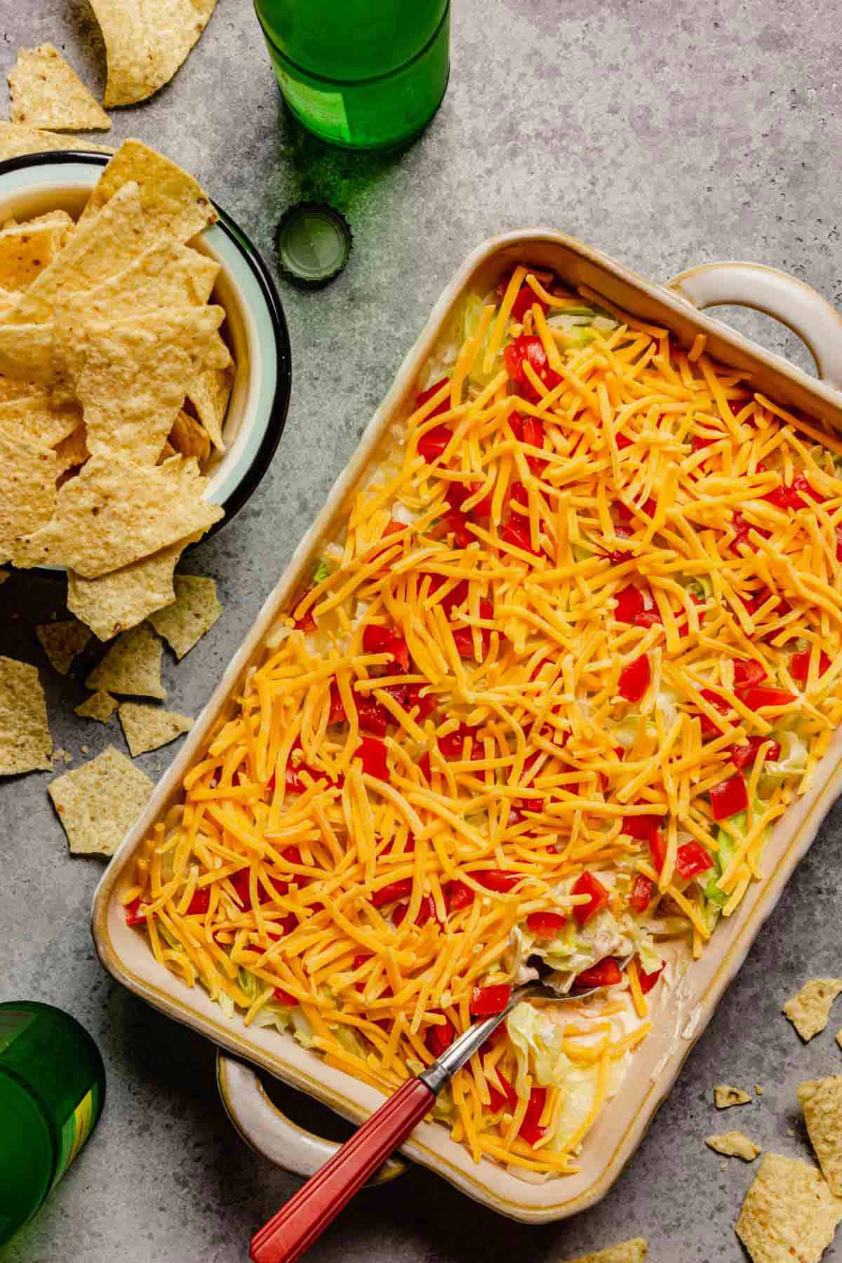 Cheesy no-bake taco dip in a casserole dish with a spoon in the right corner of the dip and a bowl of tortilla chips to the left of the dip.