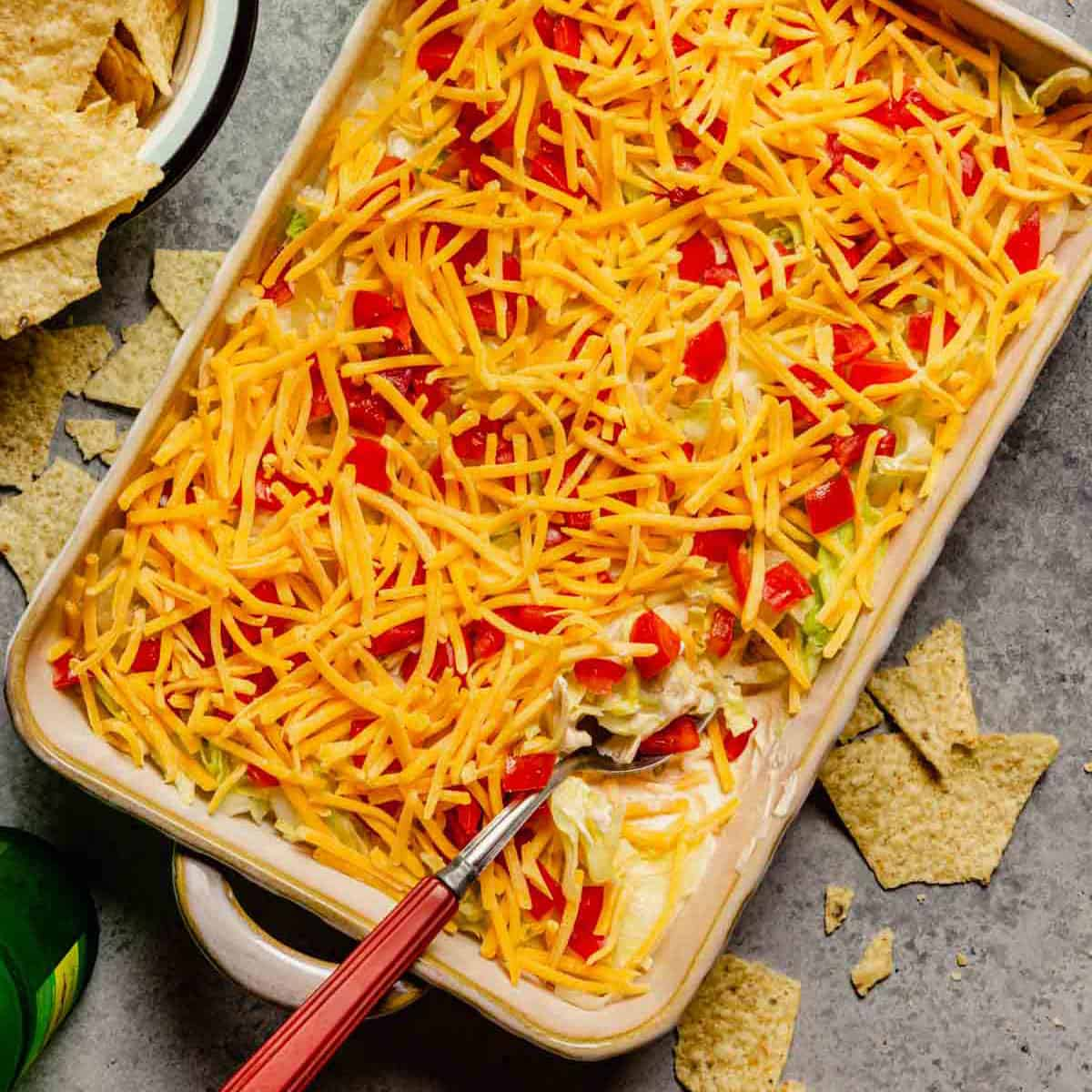 A square photo of taco dip with a spoon and a bowl of tortilla chips to the left.