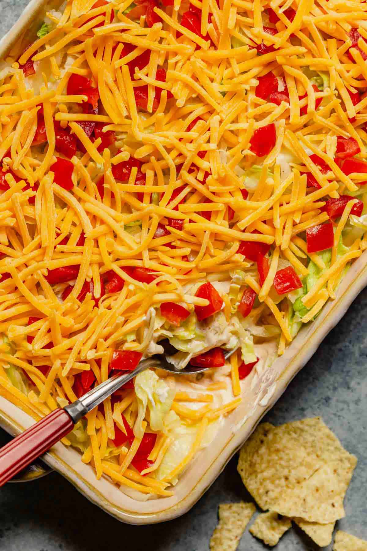 A casserole dish with taco dip and a red handled spoon in the bottom right corner on a counter with a few tortilla chips.