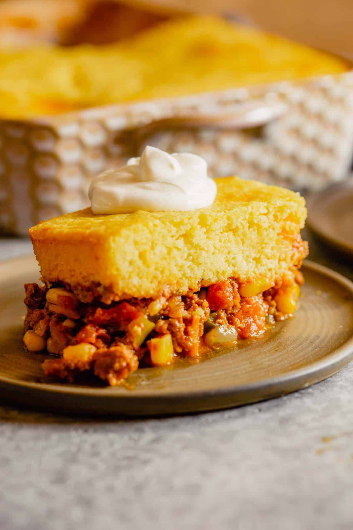A brown plate topped with a serving of tamale pie in front of a casserole dish.
