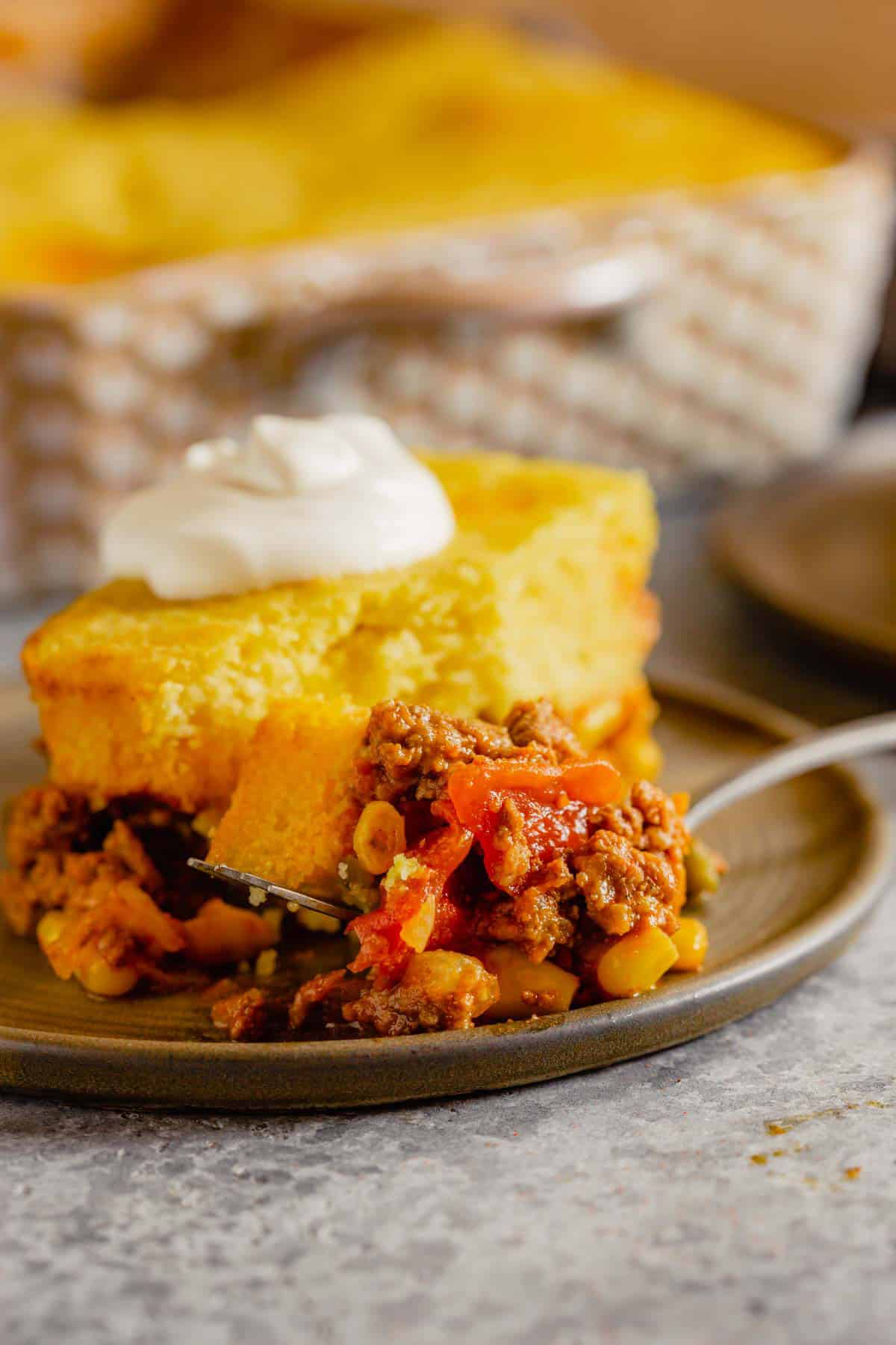 A piece of tamale pie on a brown plate with a fork topped with tamale pie.