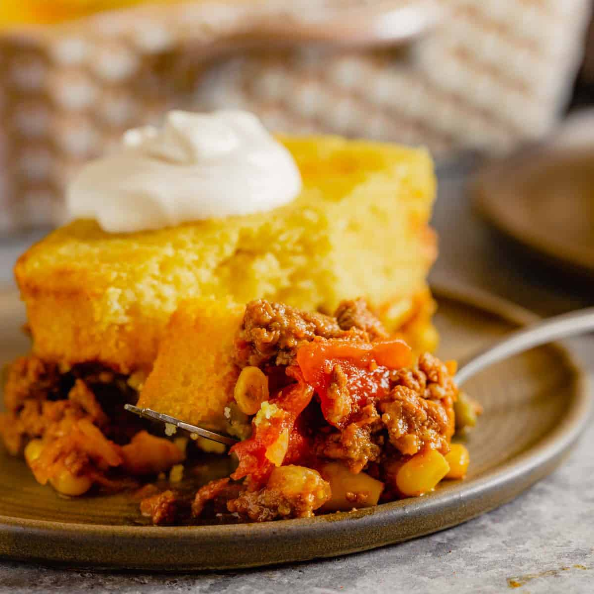 A square photo of tamale pie on a brown plate topped with sour cream.