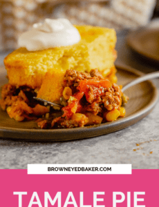 A piece of tamale pie on a brown plate with a fork topped with tamale pie with a pink rectangle at the bottom that says Tamale Pie.