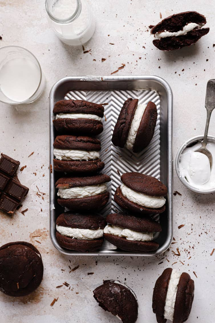 A top down photo on a rimmed baking sheet with whoopie pies on their side with a bowl of marshmallow fluff to the right and other whoopie pies on the counter around.