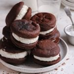 A square photo of a white plate with whoopie pies piled on top with a small glass of milk in the back.