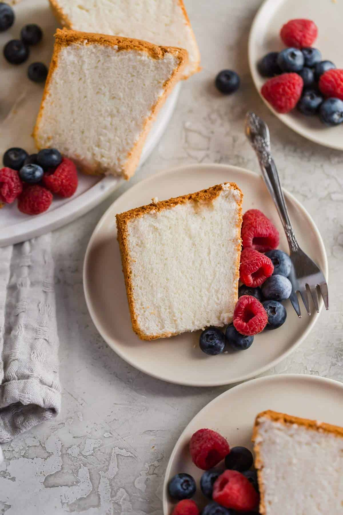 Slices of angel food cake on plates with blueberries and raspberries.