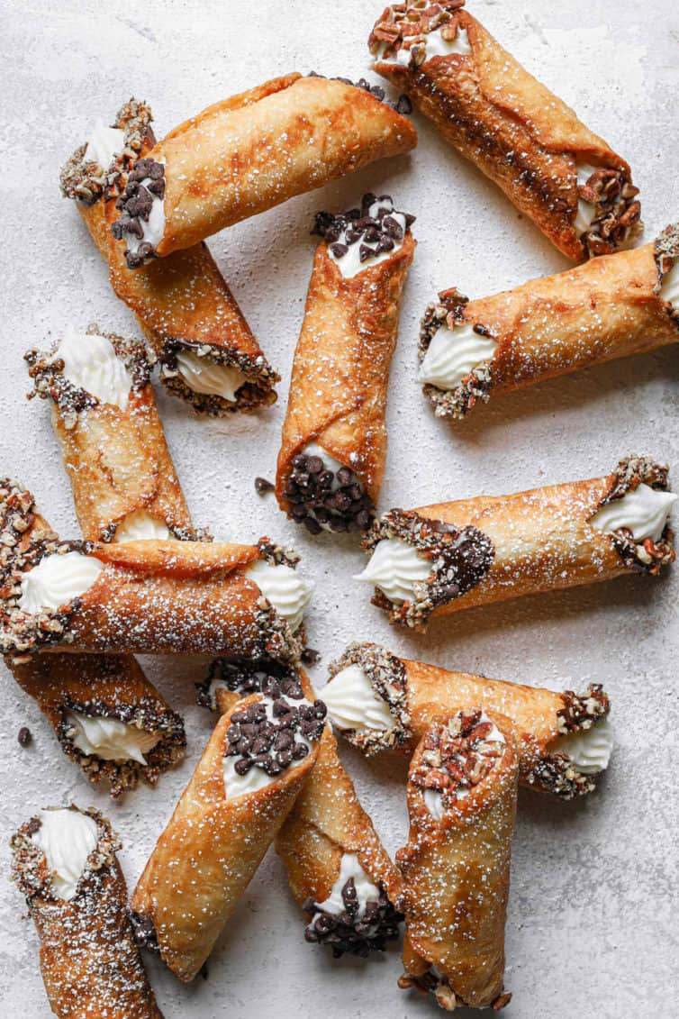 A counter with various cannolis dipped in nuts or chocolate.