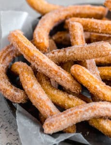 A pie pan lined with parchment paper and topped with fresh fried churros.