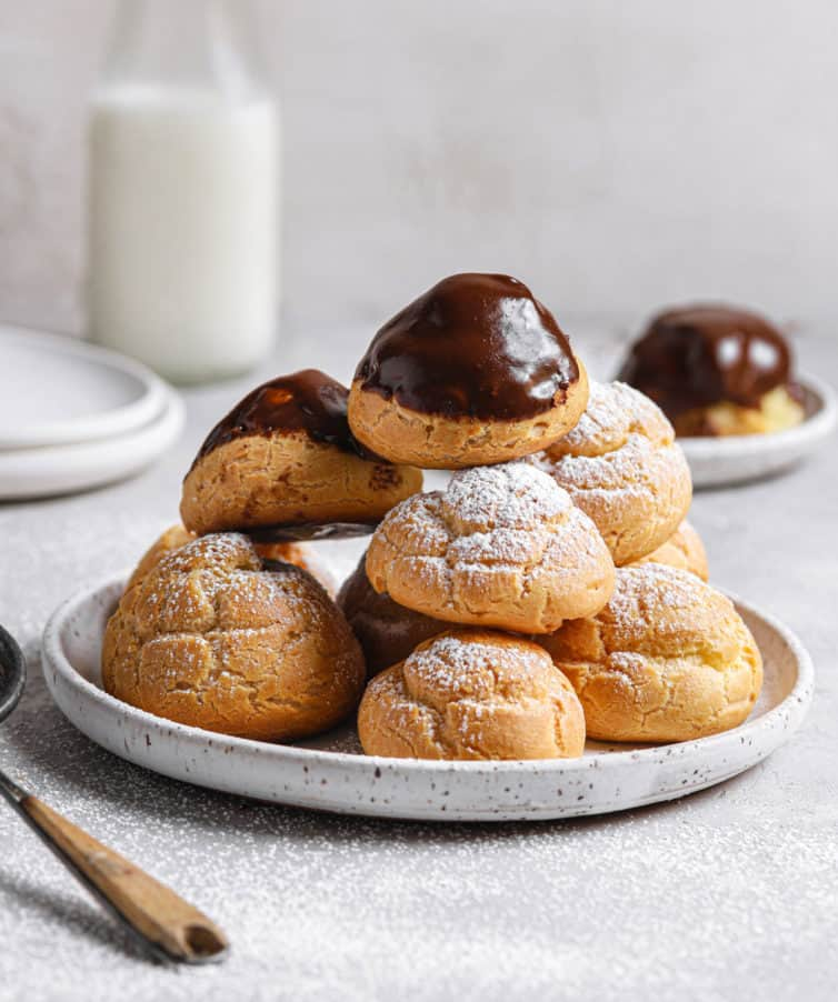 A white plate of chocolate topped cream puffs with powdered sugar cream puffs in a pile with a milk jug in the back.