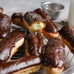 A cooling rack with chocolate dipped eclairs and one on top missing a bite to show the pastry cream inside.