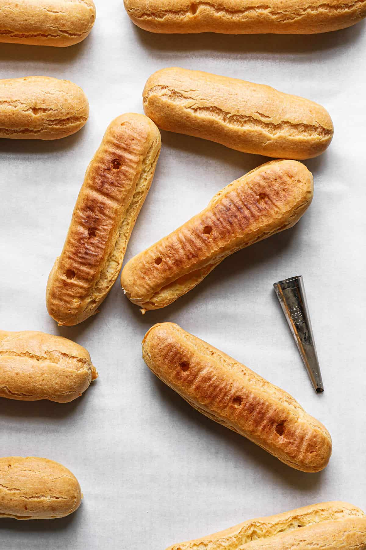 Empty eclair shells on a piece of parchment paper with holes poked in the bottom and a piping tip to the right.