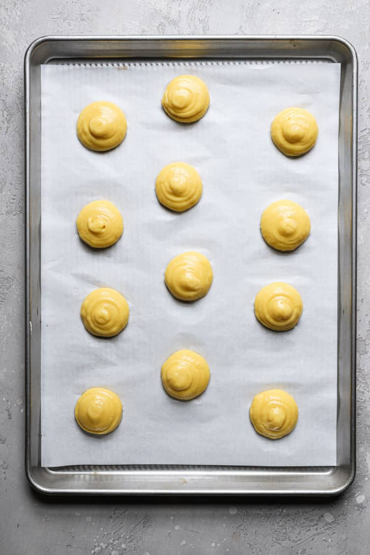 A rimmed baking sheet with a piece of parchment paper with round choux pastry puffs before baking.