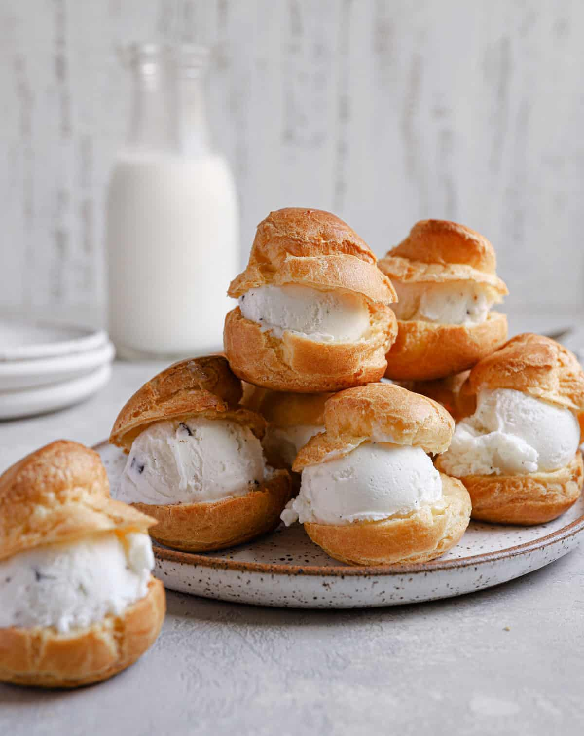 Pate a choux puffs split in half with ice cream in the middle.