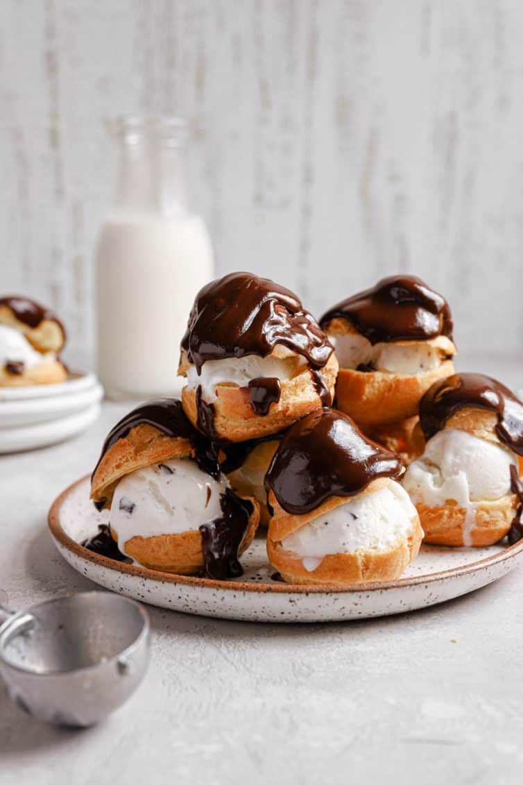 A white plate with a tower of profiteroles topped with chocolate and an ice cream scoop in the front.